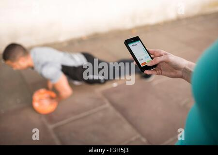 Over shoulder view of female trainer timing male runners push ups on smartphone - Stock Photo