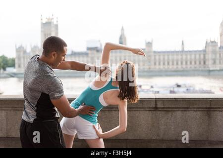 Male and female runners warming up on Southbank, London, UK - Stock Photo