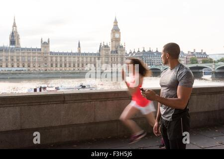 Male trainer timing female runner on Southbank, London, UK - Stock Photo