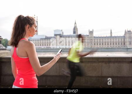 Female trainer timing male runner on Southbank, London, UK - Stock Photo