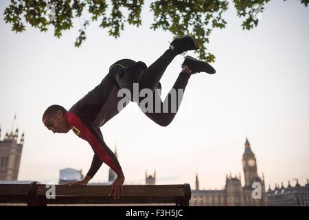Young man jumping over park bench on Southbank, London, UK - Stock Photo