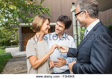 Estate agent handing keys to mature couple at new house - Stock Photo