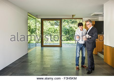 Estate agent and mature man reading paperwork at new house - Stock Photo