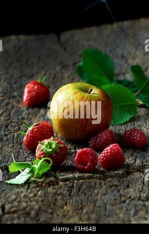 Raspberries, strawberries and apple on tree bark - Stock Photo