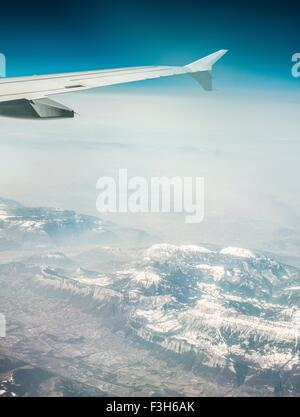 Aerial view of airplane wing and misty snow capped mountains - Stock Photo