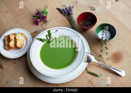 Table with fresh green soup and bread - Stock Photo