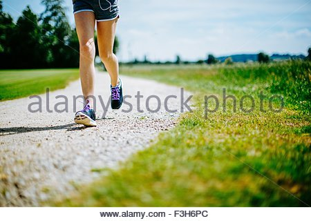 Young girl in park, running on pathway, low section - Stock Photo