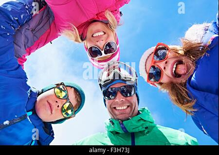 Low angle view of family in winter clothing and sunglasses - Stock Photo