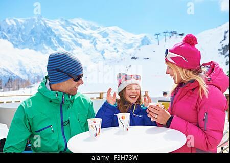 Couple having coffee with daughter, Chamonix, France - Stock Photo