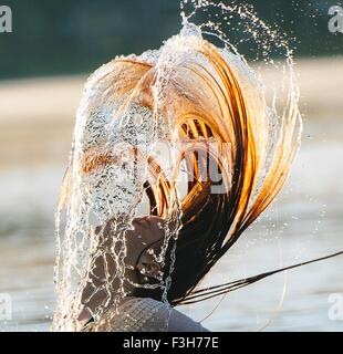 Head and shoulders of young woman in water throwing wet hair back - Stock Photo
