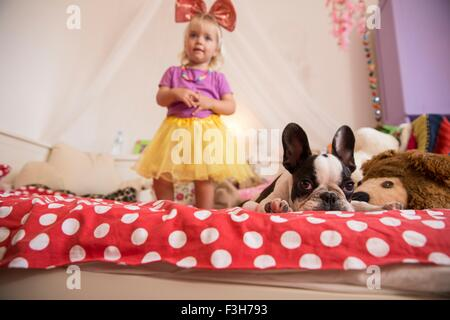 Female toddler wearing tutu and tied bow with dog on bed - Stock Photo
