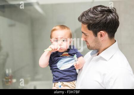 Father holding young son while son brushes teeth - Stock Photo