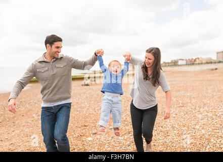 Young family walking hand in hand along pebble beach - Stock Photo