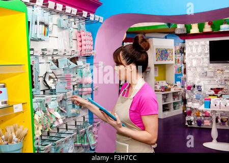 Portrait of young woman, working in cake shop, counting stock - Stock Photo