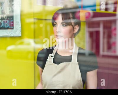 Portrait of young woman working in cake shop, taken through shop window - Stock Photo