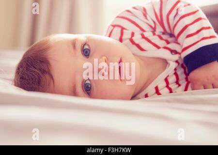 Baby boy lying on bed - Stock Photo
