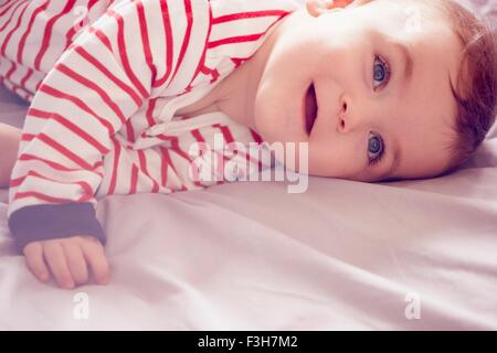Baby boy lying on bed - Stock Photo