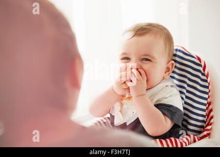 Baby boy feeding himself in baby chair - Stock Photo