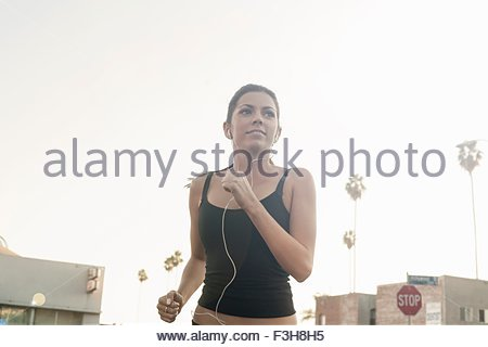 Young woman jogging in street - Stock Photo