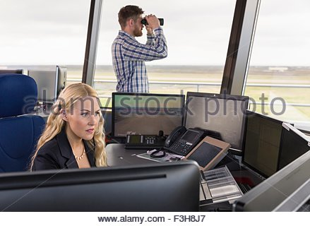 People working in air traffic control tower, monitoring screens and looking through binoculars - Stock Photo