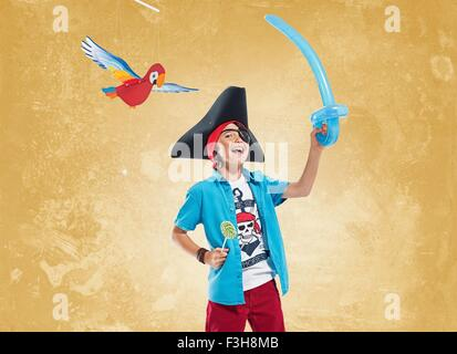 Boy wearing pirate costume and eye patch holding balloon sword and lollipop, looking at camera smiling - Stock Photo
