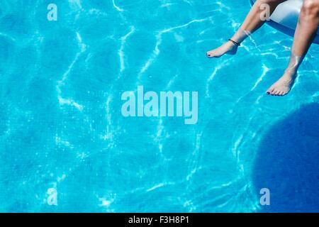 Legs and feet of teenage girl dangling in swimming pool Stock Photo
