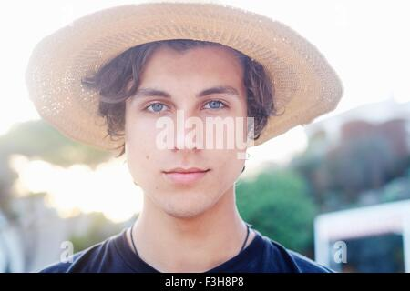 Close up portrait of young man wearing sunhat at beach - Stock Photo