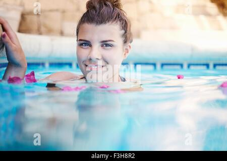 Surface level portrait of teenage girl in swimming pool - Stock Photo