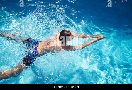 Overhead view of young man swimming in swimming pool - Stock Photo