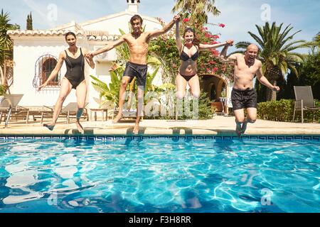 Mature couple holding hands with son and daughter jumping into in swimming pool - Stock Photo