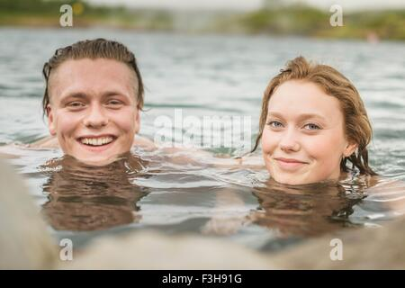 Portrait of young couple relaxing in Secret Lagoon hot spring (Gamla Laugin), Fludir, Iceland - Stock Photo
