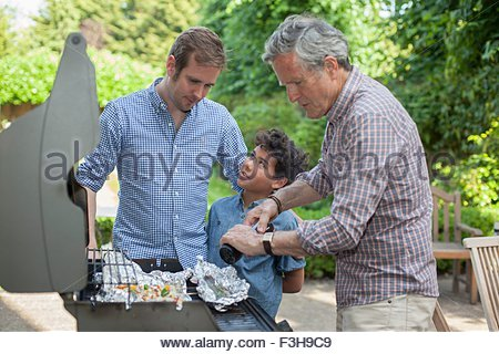 Three generation family cooking on barbecue - Stock Photo
