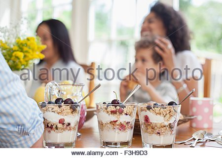 Family enjoying meal together, focus on desserts in foreground - Stock Photo