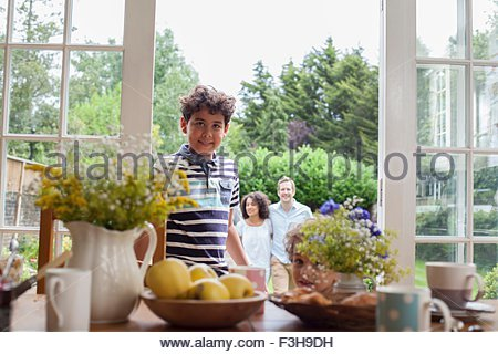 Portrait of young boy standing by patio doors, family standing behind him in garden - Stock Photo