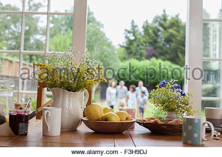 Kitchen table with breakfast foods, family in garden behind, focus on table - Stock Photo