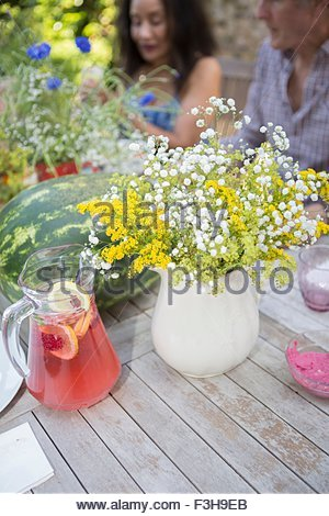 Table laid for lunch, outdoors, senior couple in background - Stock Photo