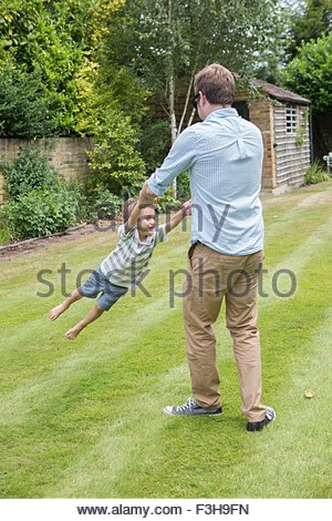 Father and son playing together in garden - Stock Photo