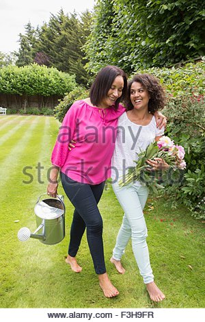 Mother and grown daughter in garden together - Stock Photo
