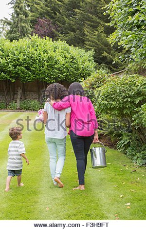 Three generation family, walking together in garden, rear view - Stock Photo