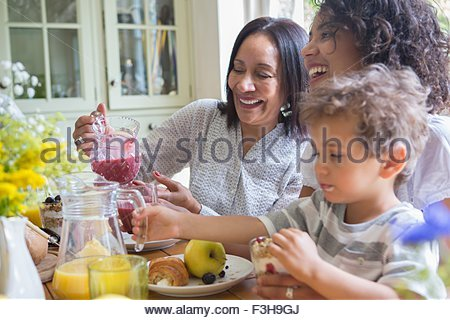 Three generation family eating breakfast together - Stock Photo