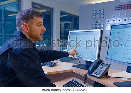 Engineer pointing at computer in control room at geothermal power station - Stock Photo