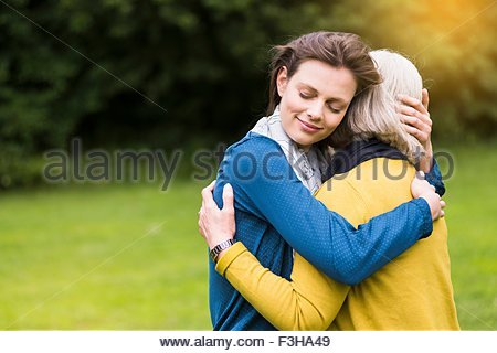Senior woman and daughter hugging tenderly in park - Stock Photo