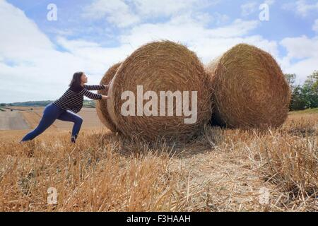 Young woman pretending to push haystacks in harvested field