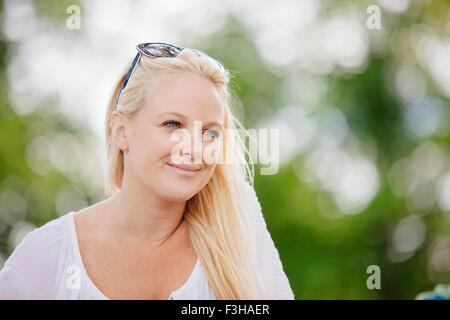Portrait of long haired blonde young woman with sunglasses on head looking away smiling - Stock Photo