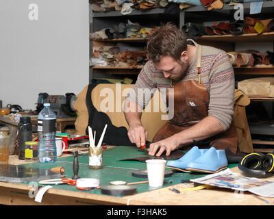 Shoemaker working in workshop - Stock Photo