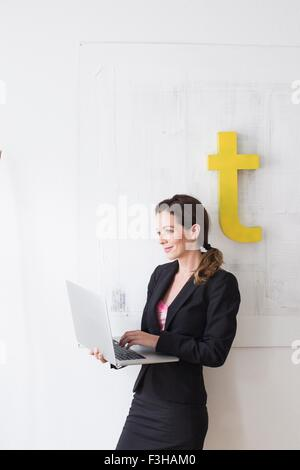 Mature woman wearing business attire standing using laptop
