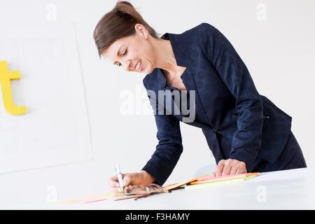 Mature woman wearing business attire writing on paperwork, looking down smiling - Stock Photo