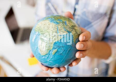Cropped view of mature women hands holding small globe - Stock Photo