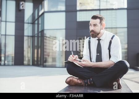 Stylish businessman sitting cross legged making diary notes from smartphone outside office - Stock Photo