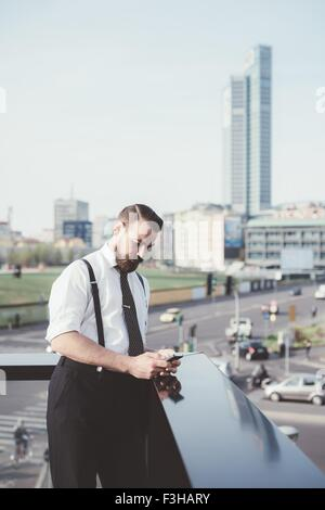 Businessman reading smartphone text update on office balcony - Stock Photo